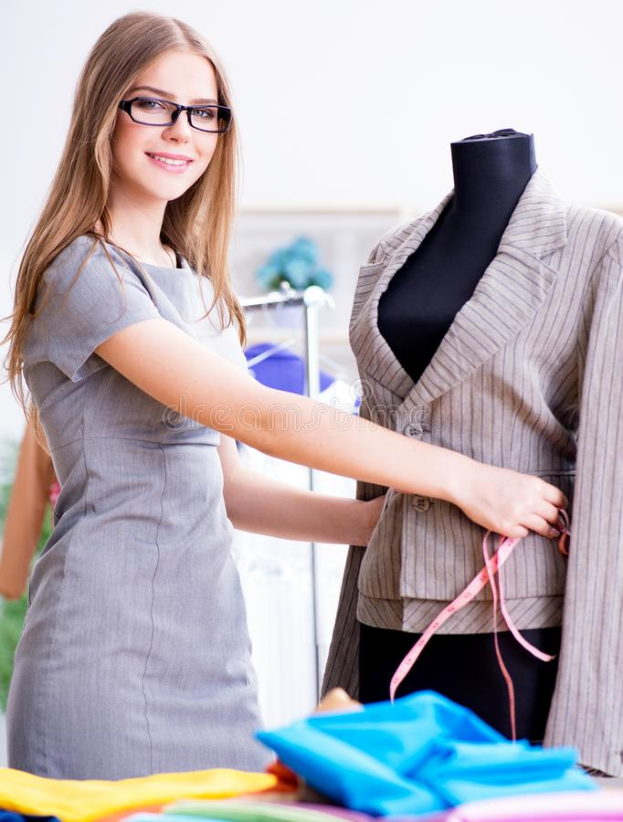 Young woman tailor working in workshop on new dress royalty free stock photo