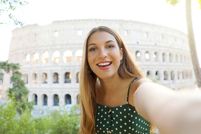 Young woman take self portrait with behind the Colosseum in Rome, Italy royalty free stock photo