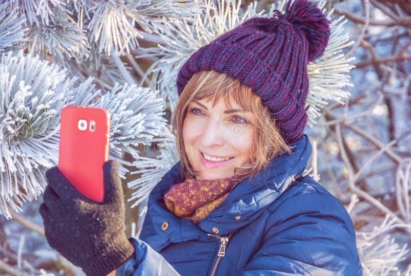 Young woman take the selfie photo, retro filter. Young caucasian woman take the selfie photo in winter outdoors. Snowy coniferous tree. Winter fashion. Retro royalty free stock photo