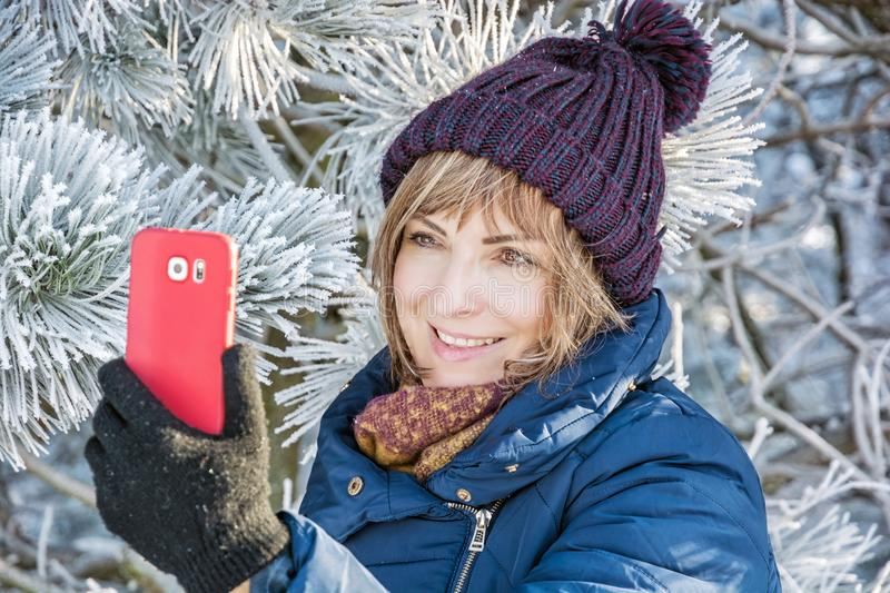 Young woman take the selfie photo in winter outdoors. Young caucasian woman take the selfie photo in winter outdoors. Snowy coniferous tree. Winter fashion stock image