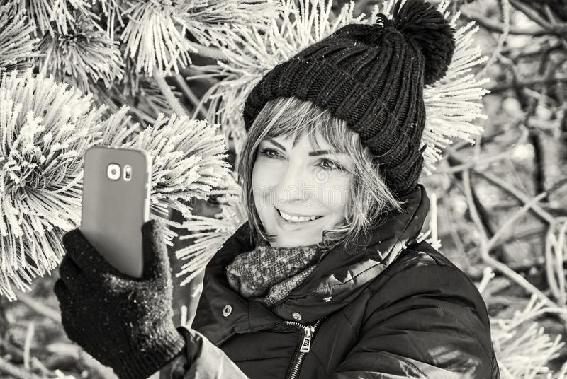Young woman take the selfie photo in winter. Young caucasian woman take the selfie photo in winter outdoors. Snowy coniferous tree. Winter fashion. Black and royalty free stock image