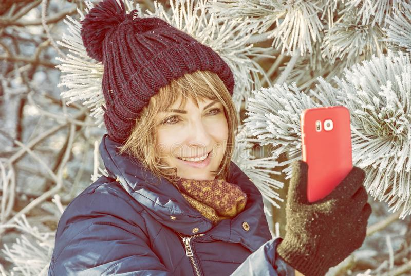 Young woman take selfie in winter outdoors. Young caucasian woman take the selfie photo in winter outdoors. Snowy coniferous tree. Winter fashion. Yellow photo stock images