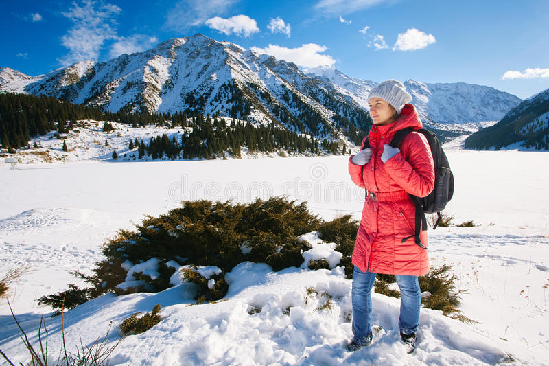 Young woman take a walk on winter mountain slope (Big Almaty Lake, Kazakhstan) royalty free stock images
