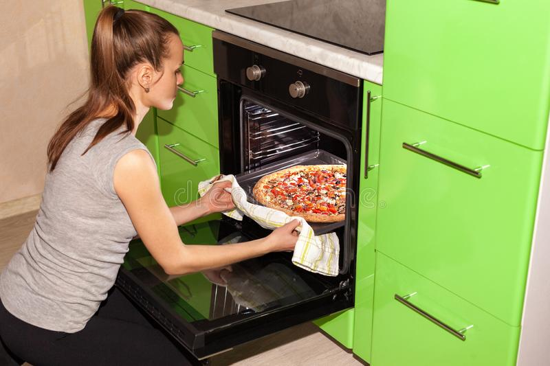 Girl baking pizza in the oven royalty free stock image