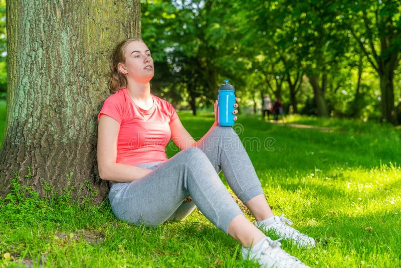 Young woman takes a break from sport and sits under a tree stock photography