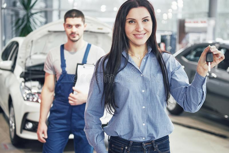 A young woman takes a car from the car service center. She is happy because the work is done perfectly royalty free stock photography