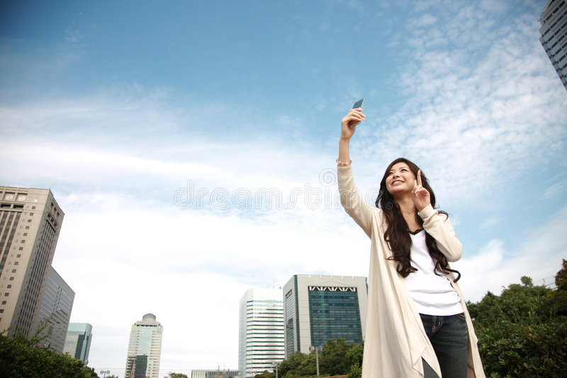 Young woman takes herself in downtown. Photographed in Chiba,Makuhari city,Japan stock photography