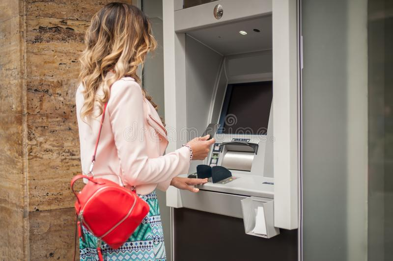 Woman traveler takes out money at an ATM in Europe stock image