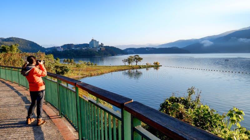 A young woman takes a photo of a beautiful natural scenery at Sun Moon Lake, Taiwan royalty free stock images