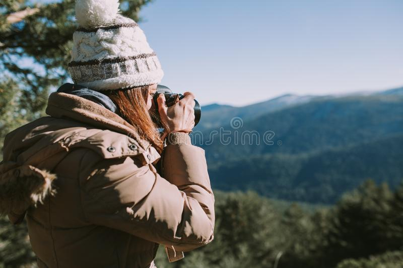 Young woman takes a photograph to the mountains royalty free stock images