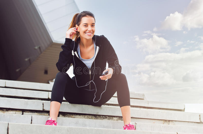 Young woman taking a break from exercising outside with cellphone. Sitting stock image