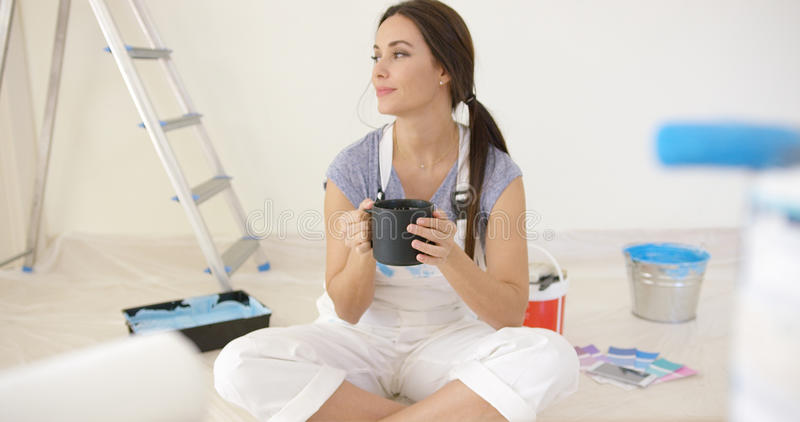 Young woman taking a coffee break. While redecorating her home sitting on the ground cross-legged staring off to the side royalty free stock photo