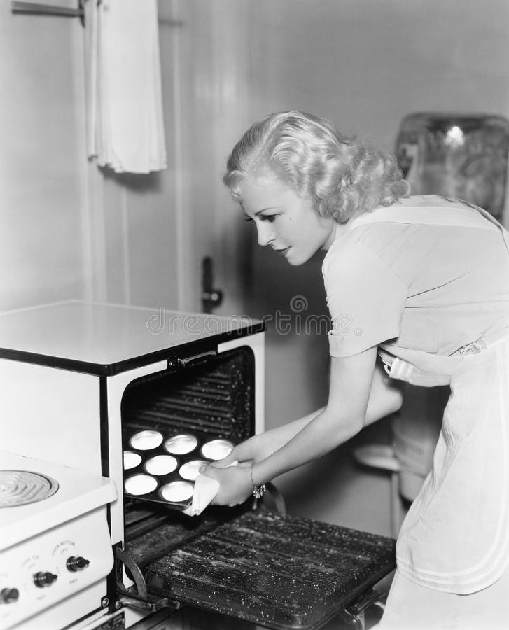 Young woman taking cookies out of an oven royalty free stock photo
