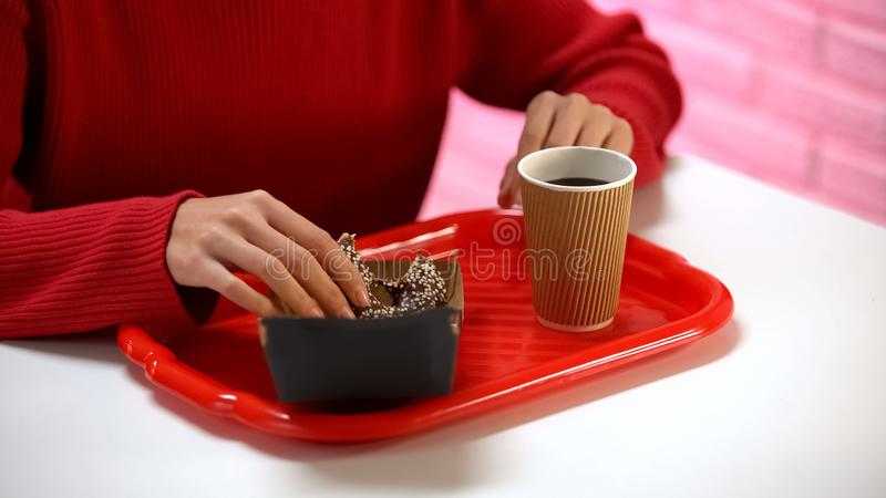 Young woman taking glazed chocolate donut from box, coffee on table, dessert stock images