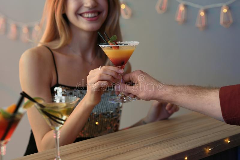 Young woman taking martini cocktail from barman at party. Closeup royalty free stock images