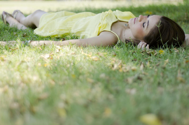 Young woman taking a nap in a park. Cute young woman resting and napping at a park stock photos
