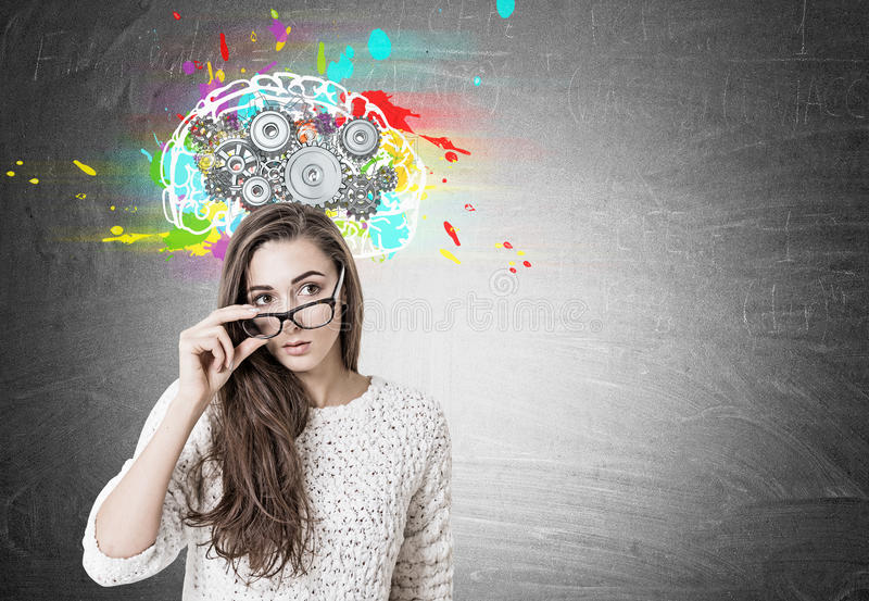 Young woman taking off glasses, brain, cogs. Young woman wearing a white sweater and holding her glasses with a thick frame. She is looking to the distance while stock images