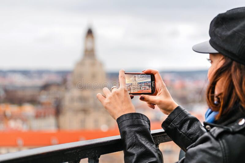 Woman taking a photo on her smartphone of a Dresden city with Frauenkirche landmark. Young woman taking a photo on her smartphone of a Dresden city with royalty free stock images