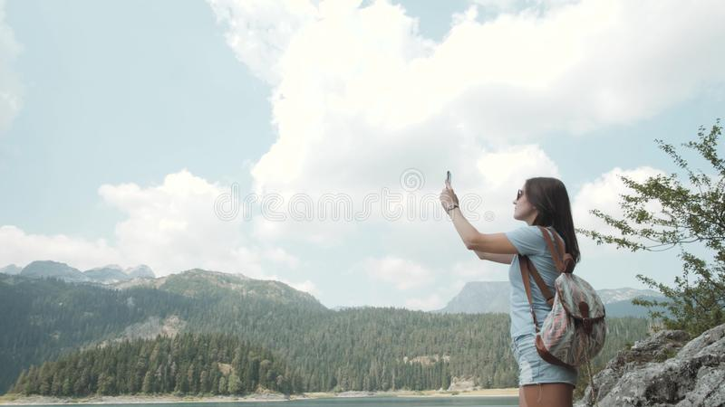 Young Woman Taking Photo By Smartphone In Front of Mountain Lake. Beautiful Caucasian Girl Spending Time In a Moutain royalty free stock image