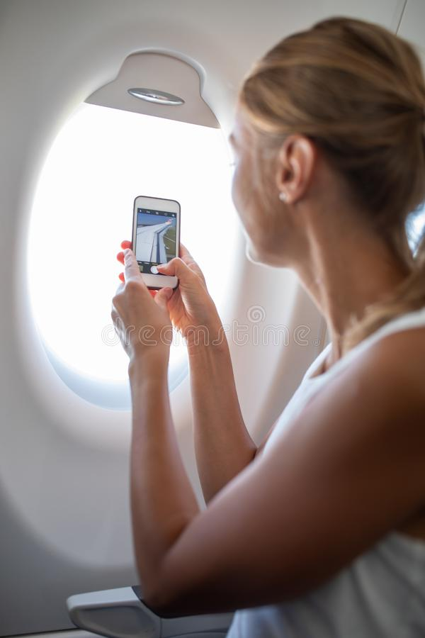 Young woman taking photos during flight stock image