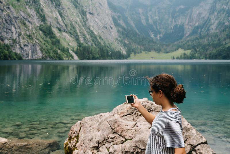 Young woman taking photos at beautiful and misty lake stock image