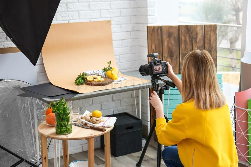 Young woman taking picture of lemons, mint stock image