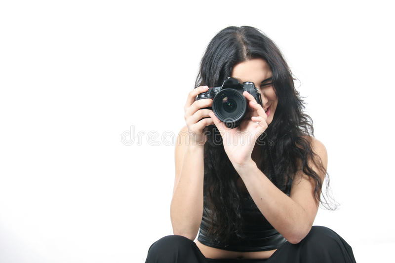 Young woman taking picture over white. Studio portrait of young woman taking picture over white royalty free stock image
