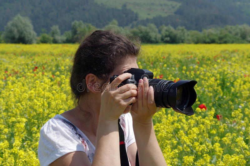 Young woman and (canola) flowers field. Spring background royalty free stock images