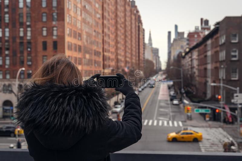 Young woman taking a picture with a smartphone in the streets of new york stock photography
