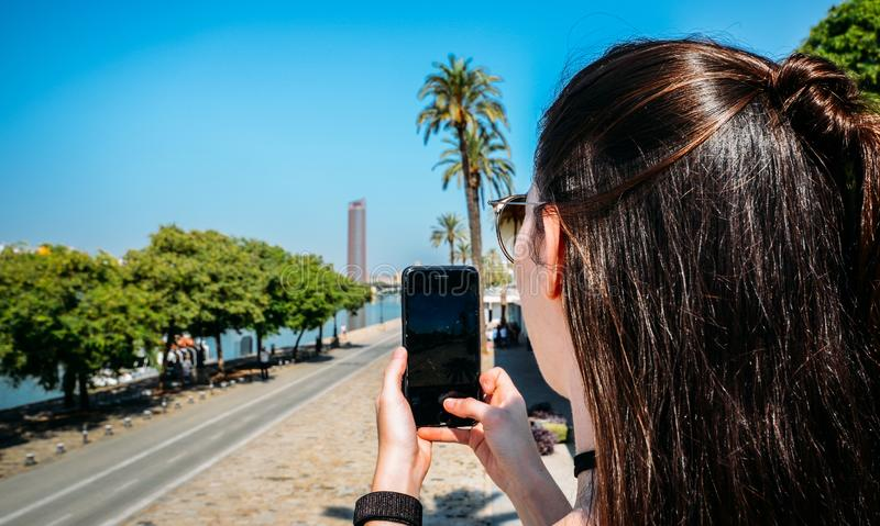 Young woman taking a picture using her smartphone of the promenade along the Guadalquivir river on a beautiful summer. Seville, Spain - Sept 9, 2019: Young woman royalty free stock images