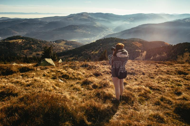 Young woman is taking pictures of a foggy valley in France royalty free stock image
