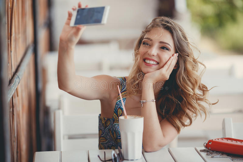 Young woman taking a selfie in a cafe royalty free stock photo