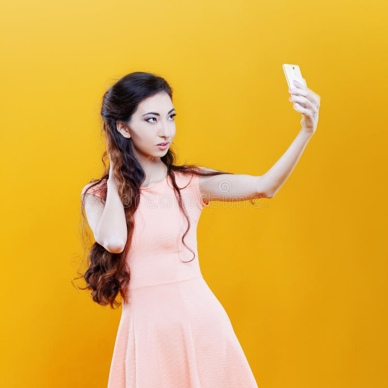 Young woman taking selfie. Fashion asian young girl taking picture of herself, selfie. Portrait on yellow background. Fashion asian girl with the camera royalty free stock photo