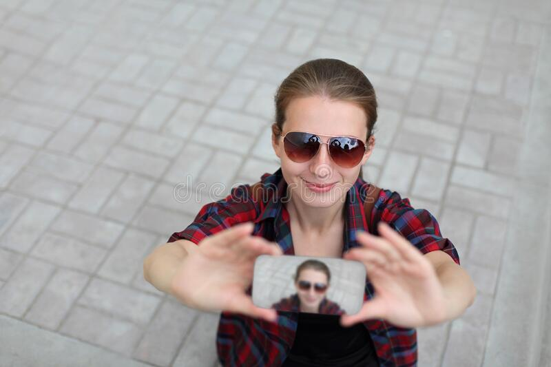 Young woman taking selfie picture by smartphone over city street background royalty free stock photography