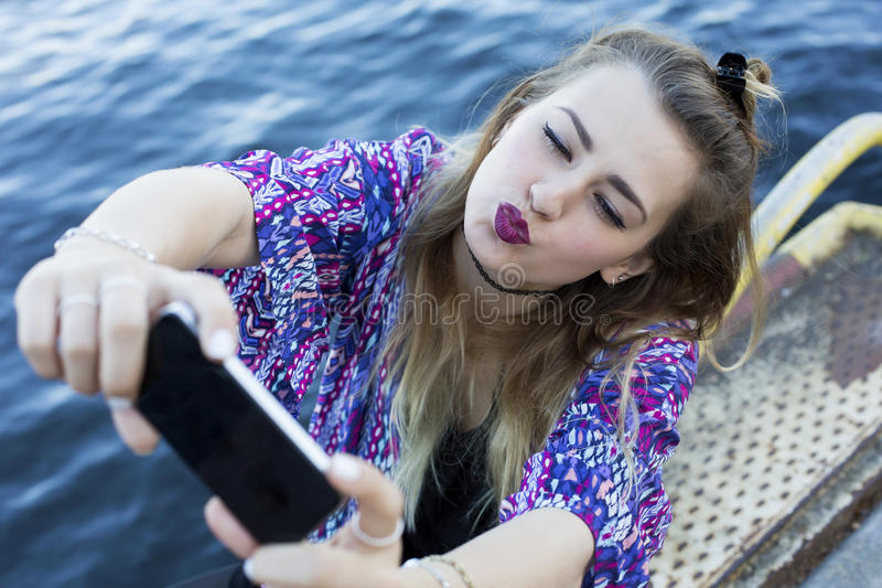 Young woman taking a selfie. Young woman by the waterfront taking a selfie royalty free stock photography
