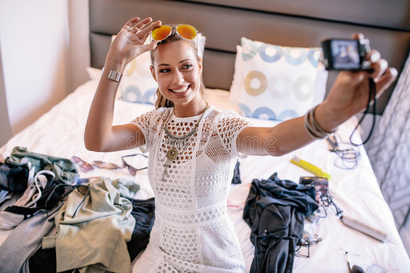 Young woman taking a selfie wearing colorful goggles. Female vlogger recording broadcast with digital camera. Woman taking a selfie video displaying fashion royalty free stock image