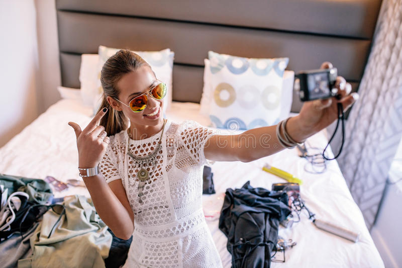 Young woman taking a selfie wearing colorful goggles. Female vlogger recording broadcast with digital camera. Woman taking a selfie video displaying fashion royalty free stock images