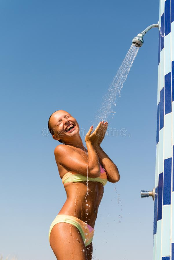 Young woman taking shower. Sensous slim woman taking shower at the beach royalty free stock photography