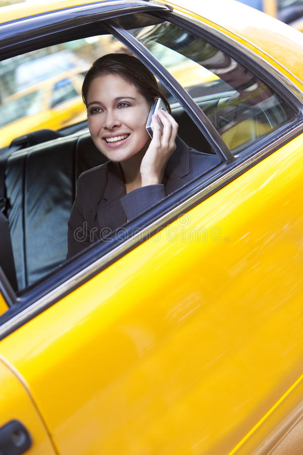 Young Woman Talking on Cell Phone in Yellow Taxi stock image