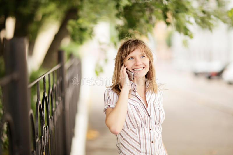 Young woman talking on cellphone outdoors royalty free stock images