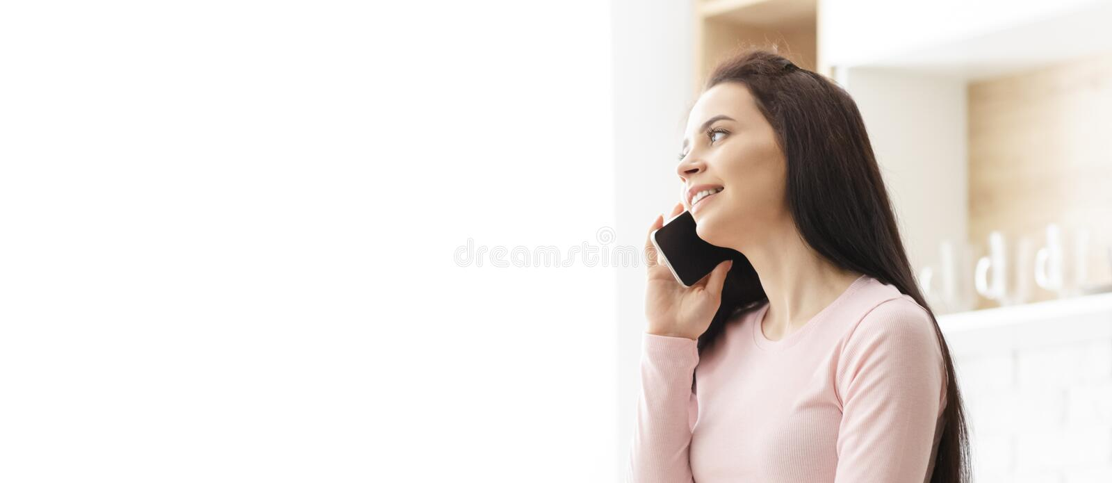 Young woman talking on her mobile phone at kitchen royalty free stock photo