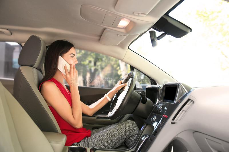 Young woman talking by mobile phone on driver's seat of car stock image