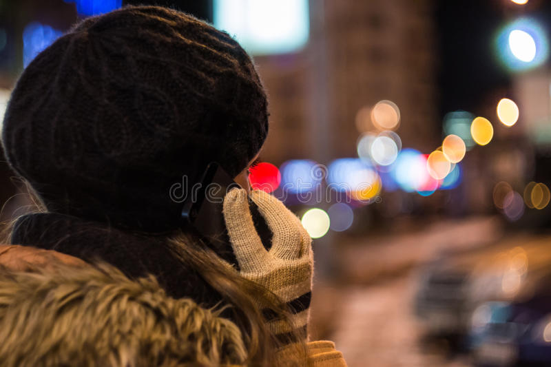 Young woman talking on mobile phone at night in winter stock images