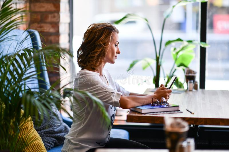 Young woman talking on a mobile phone while relaxing in a cafe, sitting on a blue armchair, relaxing in a cafe in her free time. royalty free stock image