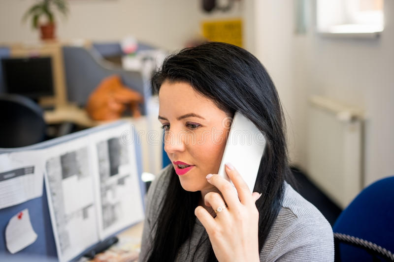 Young woman talking on mobile phone at work and advises clients. Young woman talking on mobile phone at work and advises customers stock photography