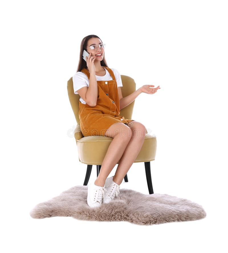 Young woman talking by phone in armchair on white stock photography