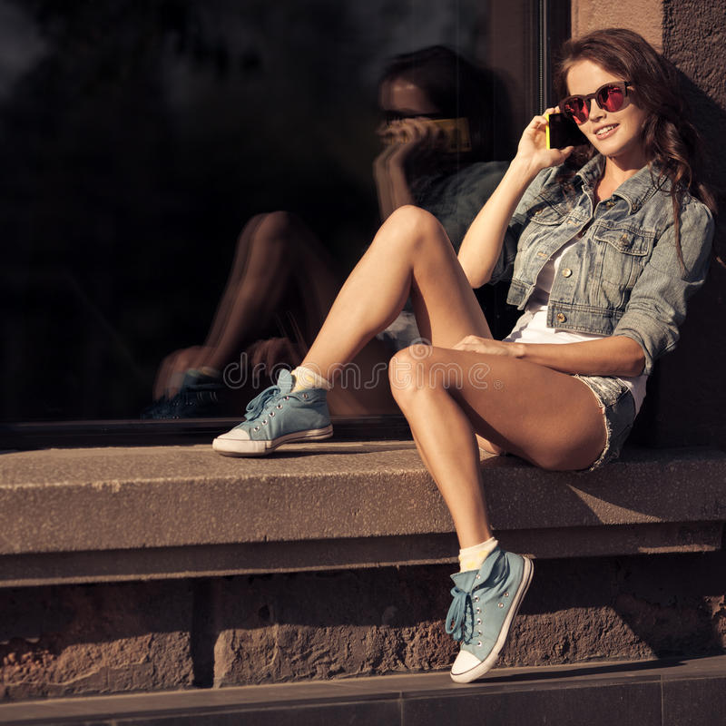 Young woman talking on phone. City street on background. stock image
