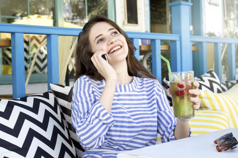 Young woman talking on the phone with a glass of lemonade in cafe. stock photo
