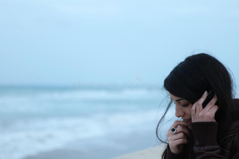 Young woman talking on the phone next to the sea in winter royalty free stock photos