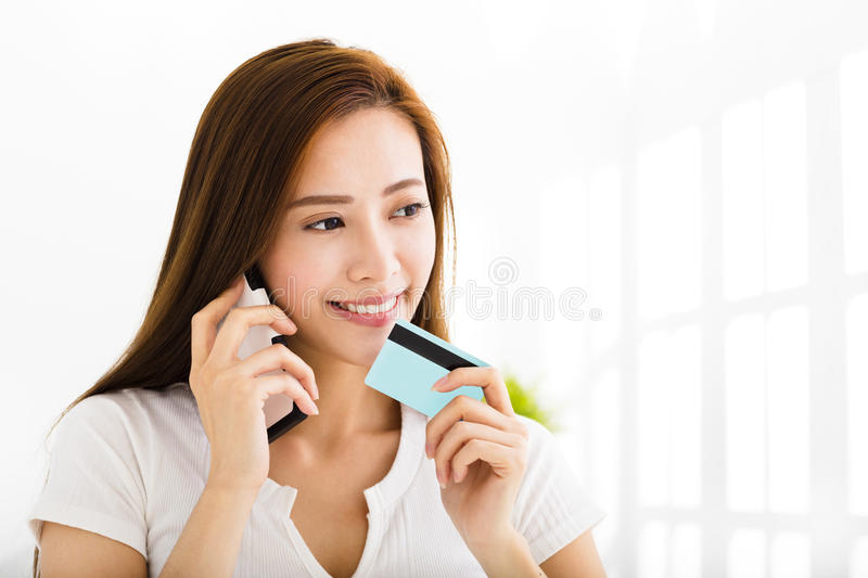 Young woman talking on the phone and showing credit card stock images